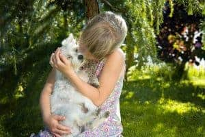 Blonde girl with bangs holding small white dog in her arms in a green wooded area.