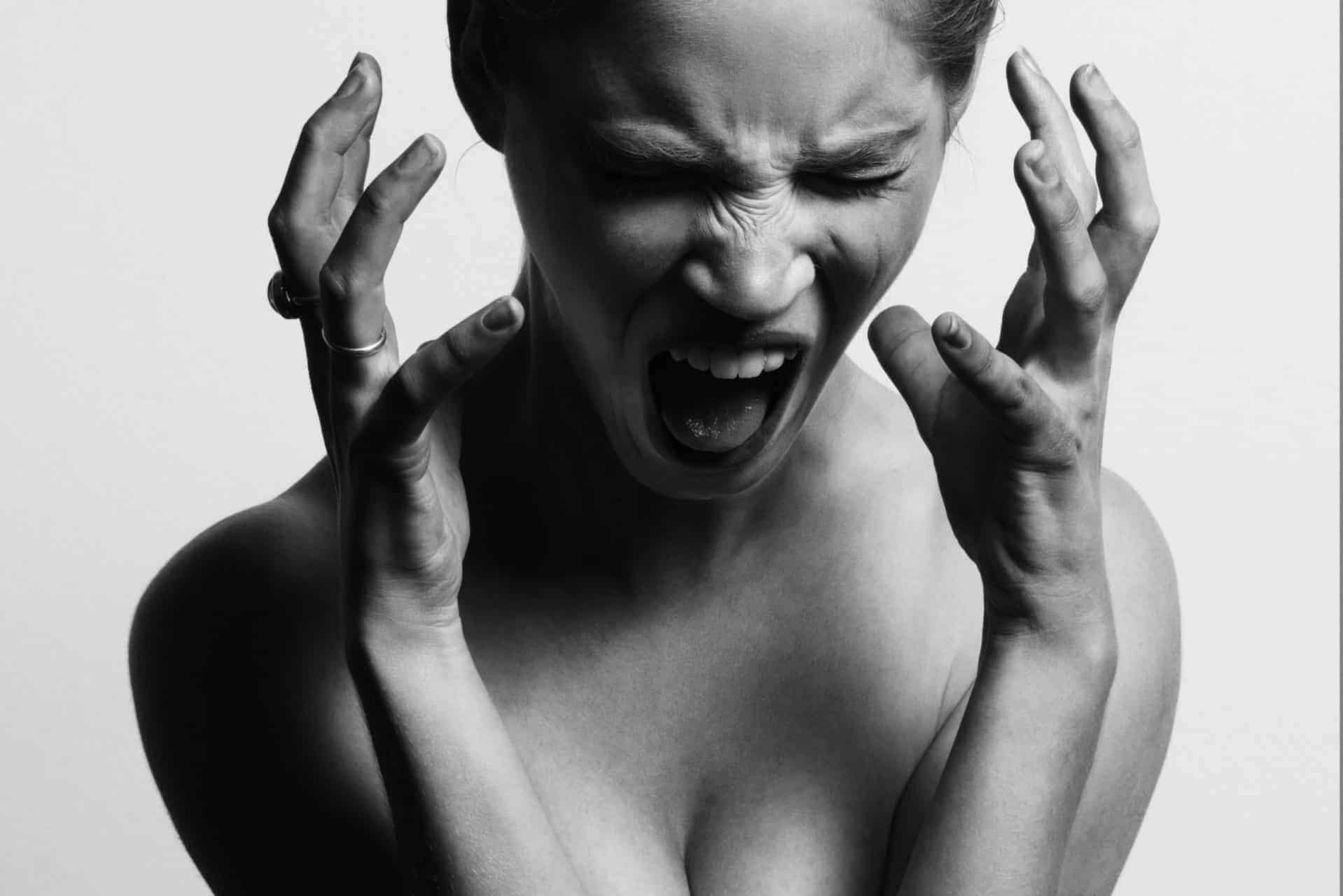 Black and white photo of super stressed woman with her hands by her face yelling