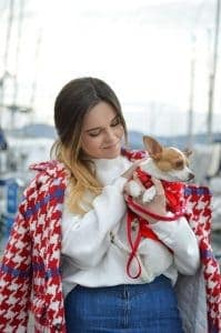 Woman wearing white and red holding a small white and tan dog wearing red in her arms