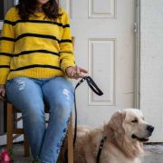 Woman wearing a striped yellow and black shirt sitting with golden retriever with a black leash.